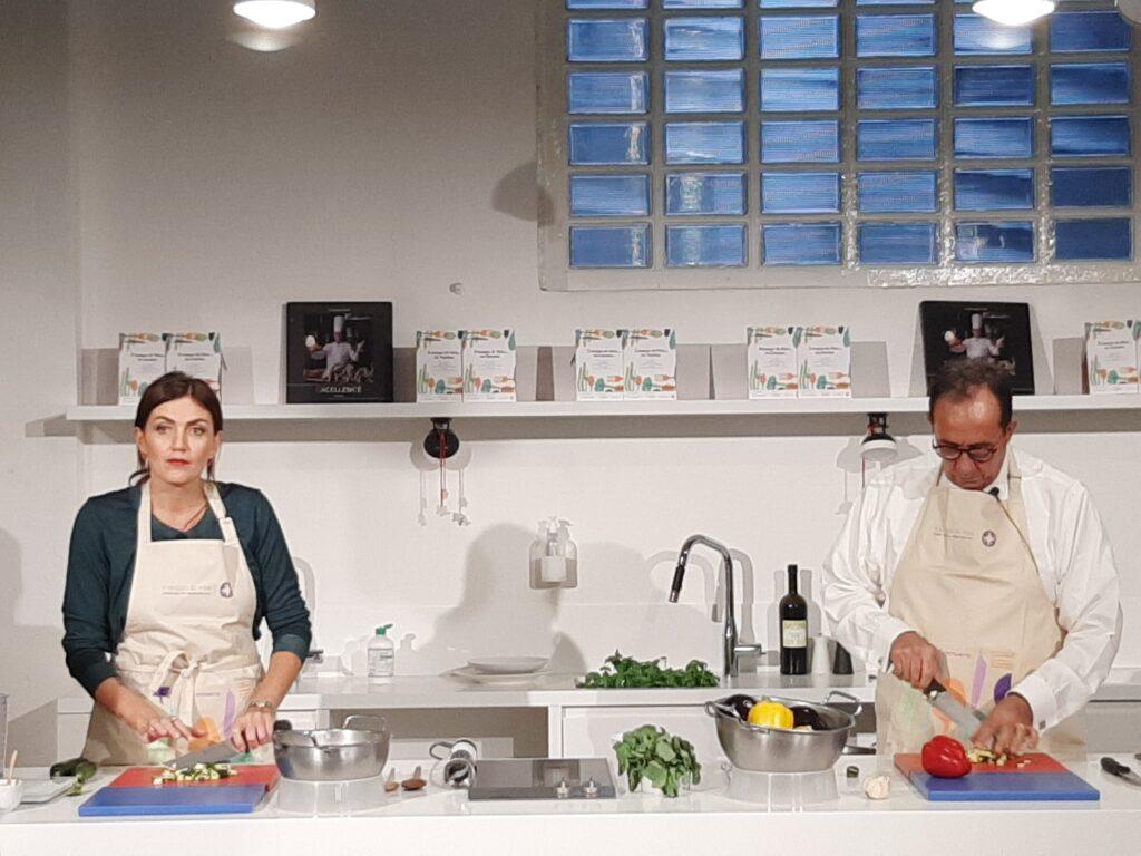 """La food blogger Chiara Maci e il professor Filippo de Braud ai fornelli durante la presentazione del ricettario """"è tempo di vita... in cucina!"""""""